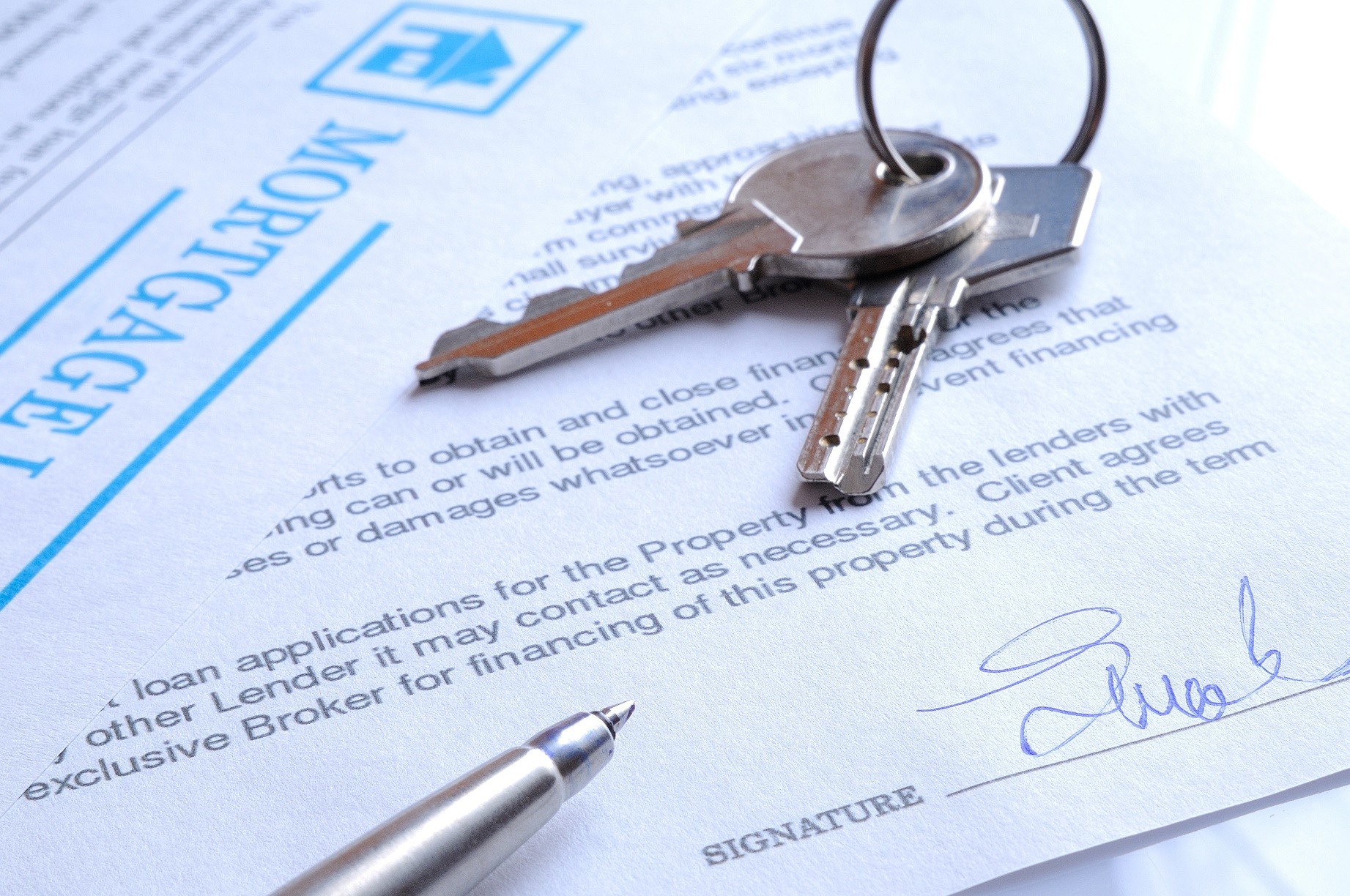 mortgage contract signed with detail of keys to buying a home closeup