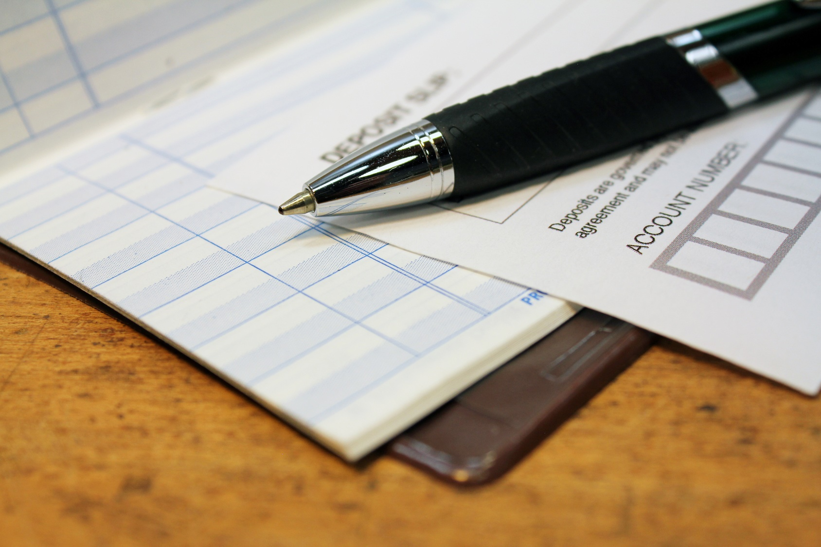 Paper deposit slip and pen with check ledger over wood background