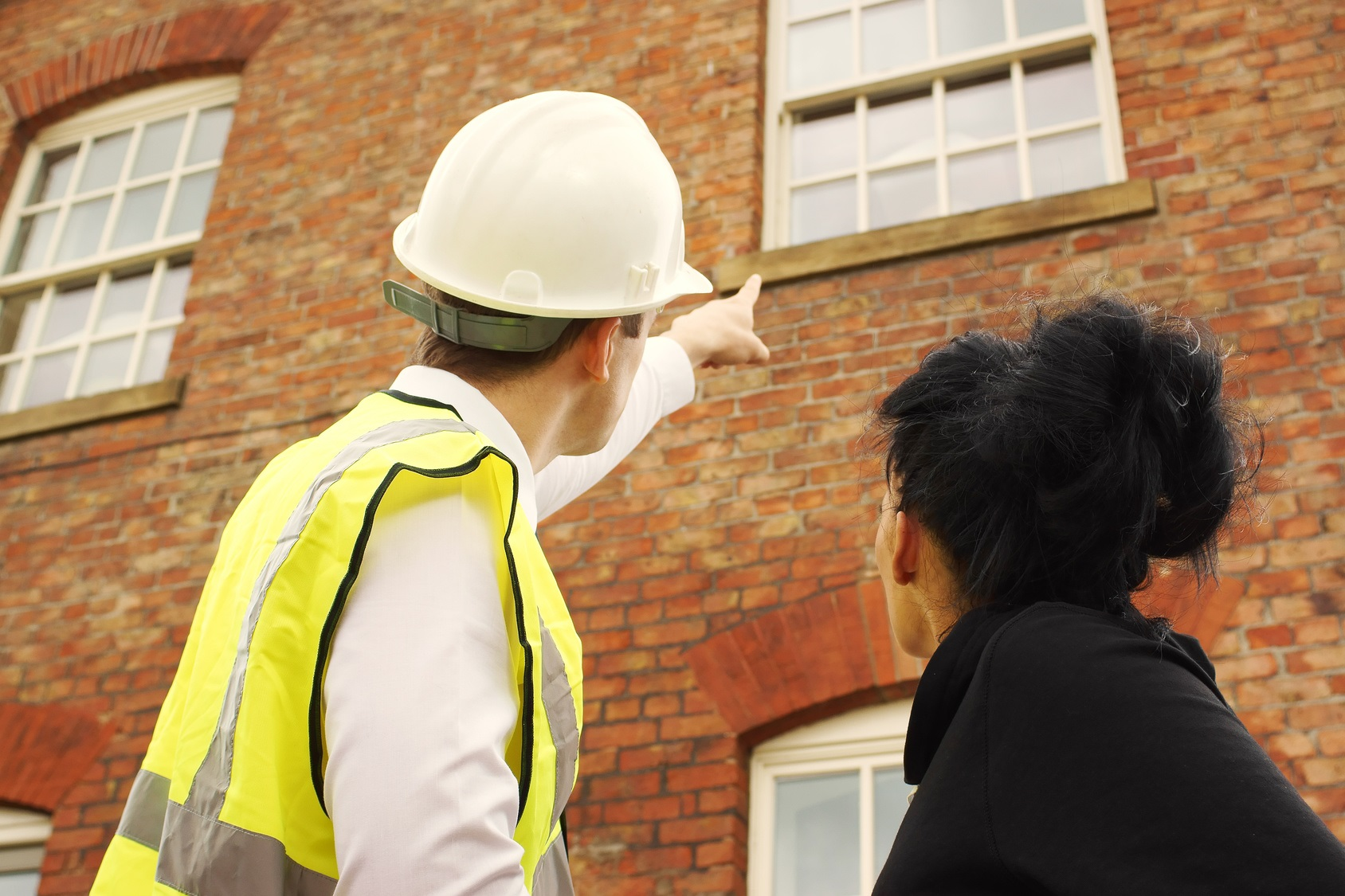 A builder, contractor or surveyor pointing out an issue with a property to a homeowner.