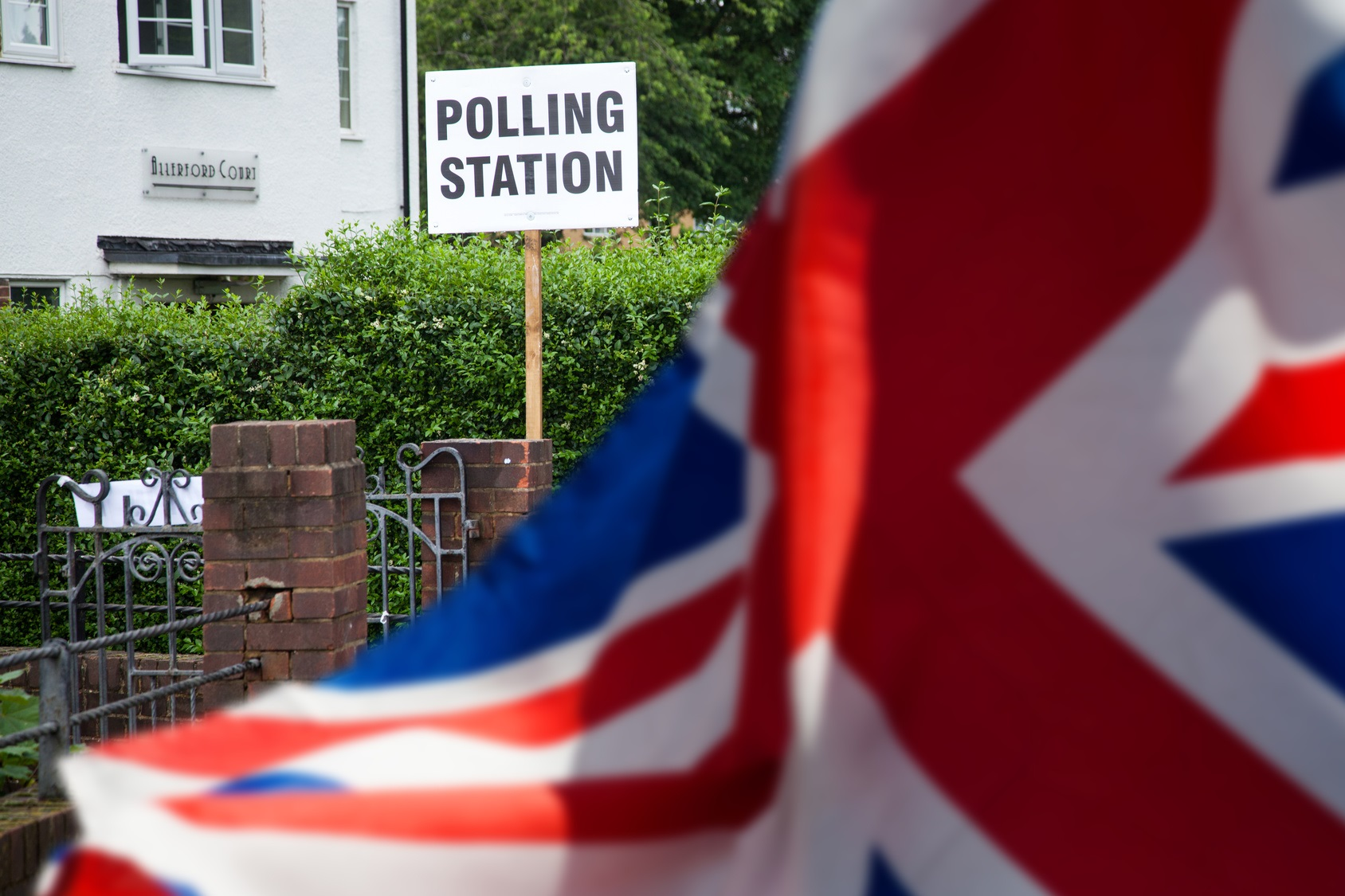 polling station sign and Union Jack flag - UK prepares for elections
