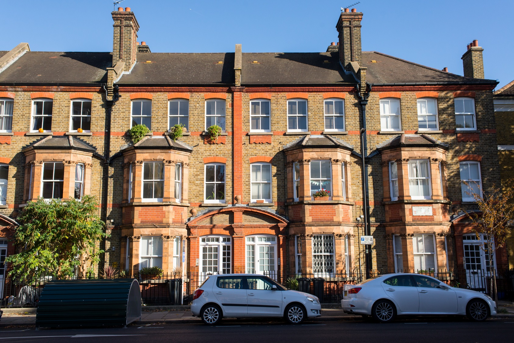 Front view of a classic English Victorian property with three floors of apartments in red and brown bricks with cars parked in front of it