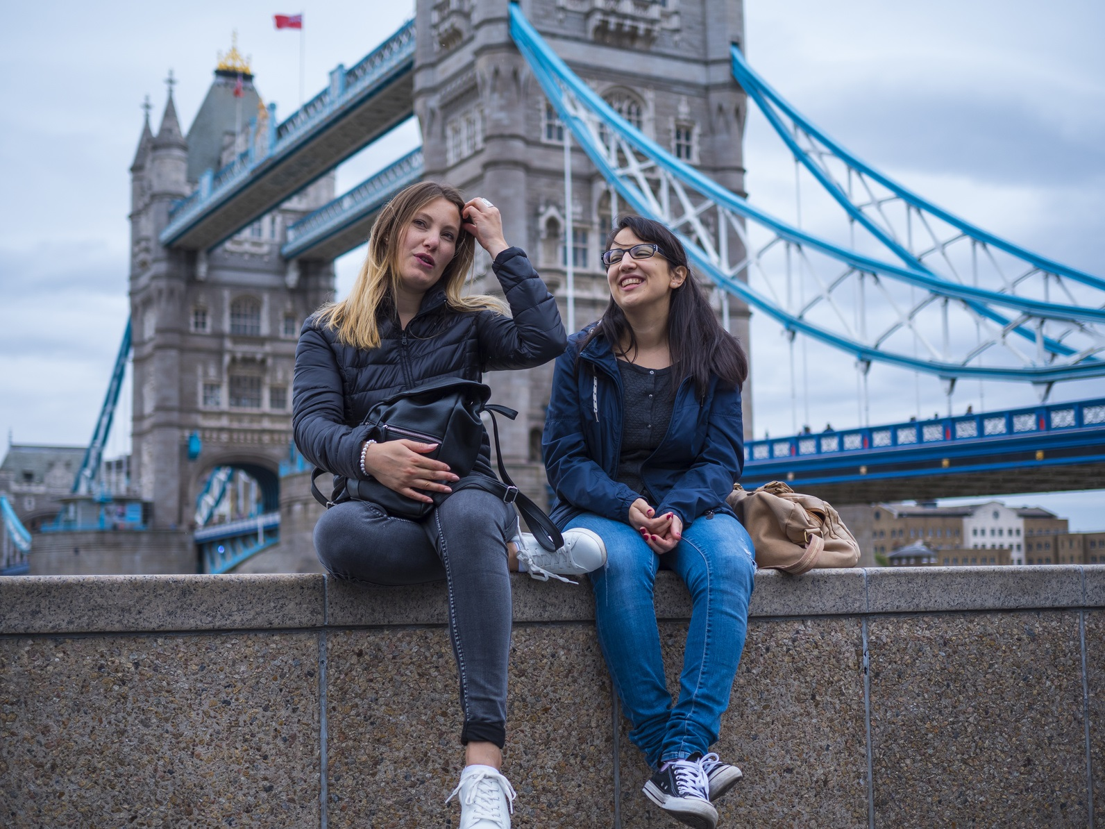 Two girls on a city trip to London - relax at the Tower Bridge