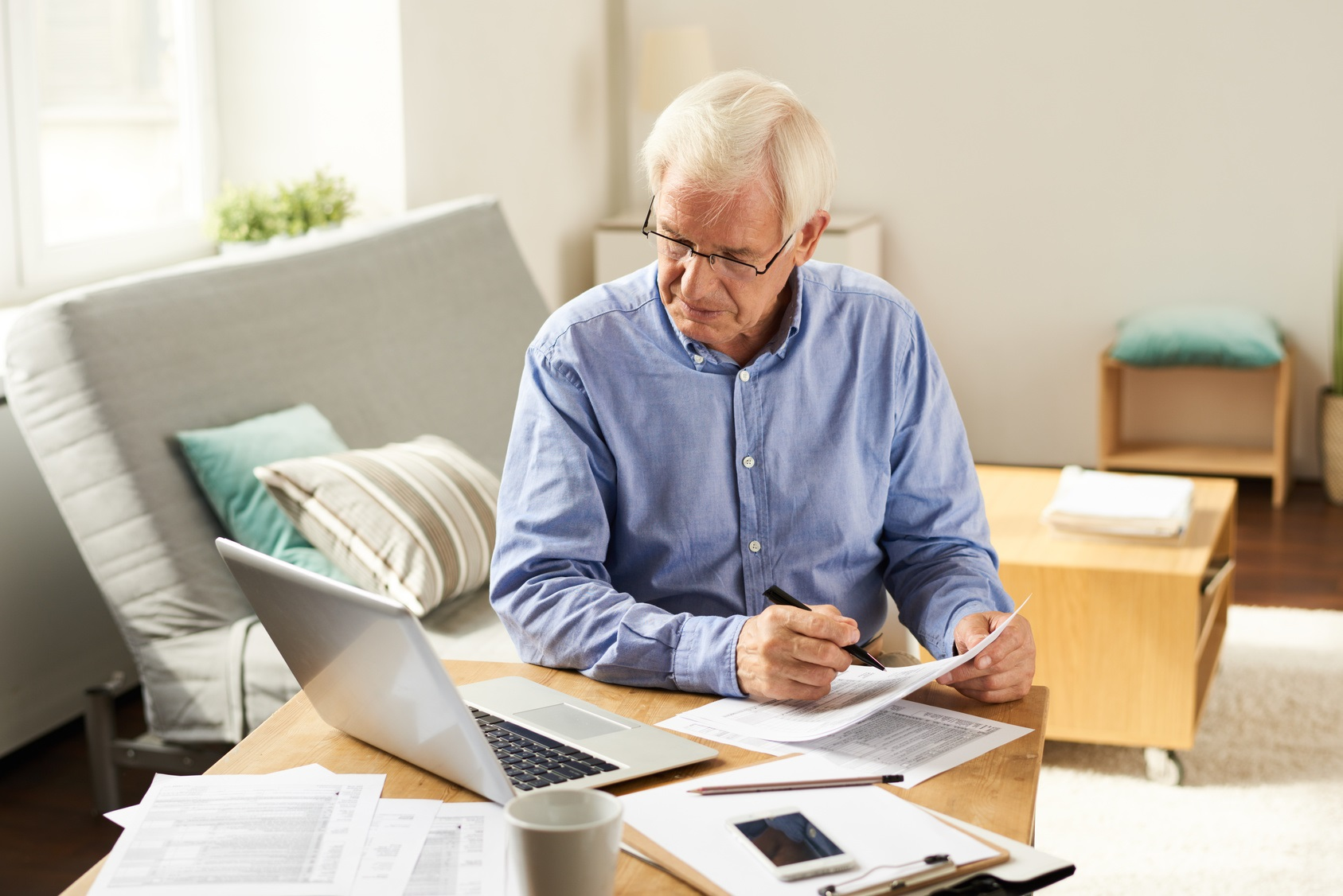 Portrait of modern senior man filling in application form  at home sitting at table with laptop in  living room