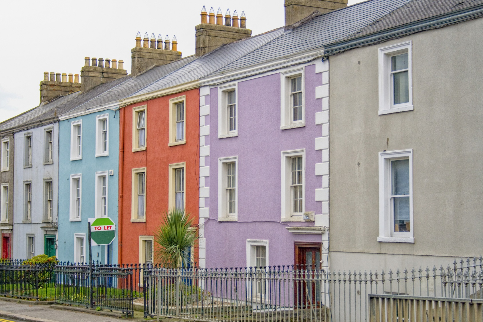 Colorful houses on a row in a Dublin street with a to let sign in front of one of them